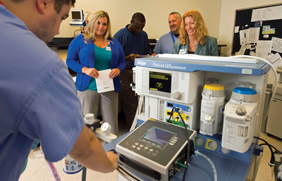 Jared Graff passes along insights from a recent anesthesia service training course to  Kelly Robinson, Julius Obazee, Matt Smith, and Karen Waninger.