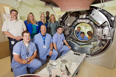 Photo of Community Health Team with an open CT scanner.