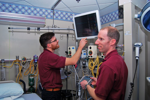Daryl Lehman and David Soffer configure a Spacelabs monitor with a simulator for connectivity testing.
