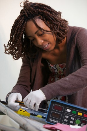 A Summer Institute participant in Trinidad works to repair a vital signs monitor.