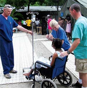 David Sieminski (L) with a patient on her first day outside after an arm amputation and liver repair from damage done by the earthquake.