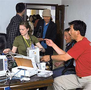 Michael Y. Young (red shirt) performs repairs during his Operation Smile mission in Yuxi, China.
